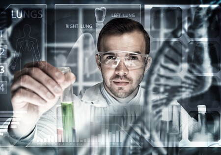 concentrate: Young scientist mixing reagents in glass flask in clinical laboratory Stock Photo