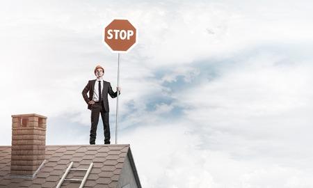interdiction: Ingénieur homme debout sur le toit de la maison et tenant un signe d'interdiction rouge. Médias mélangés