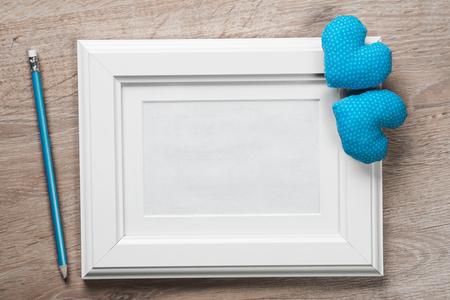 Kleine rote Herzen und Bleistift des weißen Fotorahmens auf Holztisch Standard-Bild - 81270872