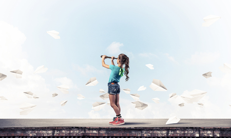 Cute kid girl standing on house roof and looking in spyglass Stock Photo