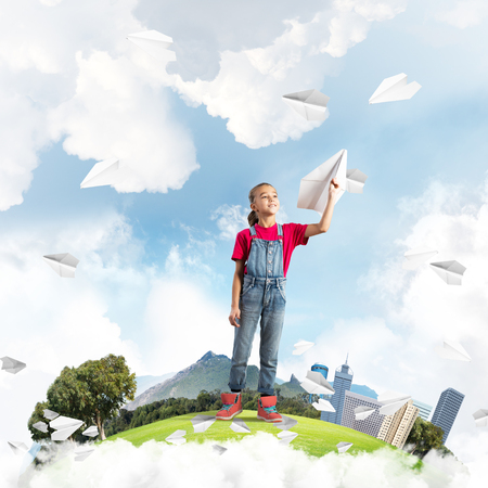 Cute kid girl on city floating island throwing paper plane Banco de Imagens