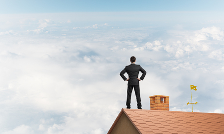 Jonge bepaald zakenman staan ??met de rug op de dak van het huis en kijkt weg. Gemengde media
