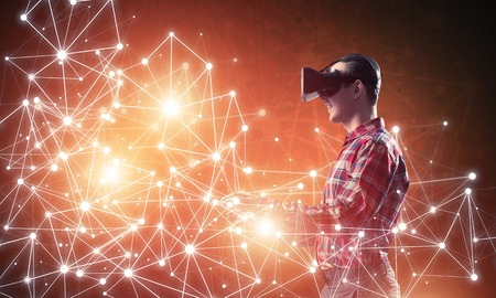 hands free device: Young man with virtual reality headset or 3d glasses among connection lines Stock Photo