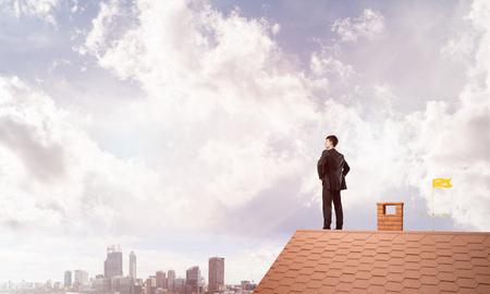 Jonge bepaalde zakenman die zich op huisdak bevindt en weg eruit ziet. Gemengde media Stockfoto