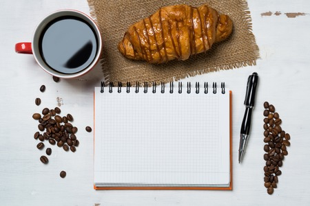 Opened notepad and cup of coffee with donut on wooden table Stock Photo