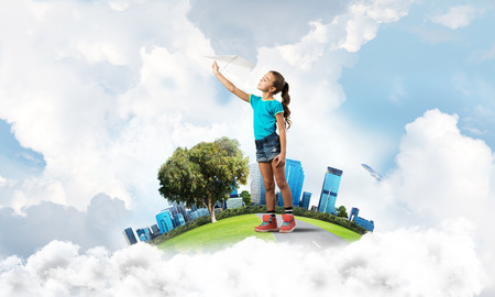 become: Cute kid girl on city floating island throwing paper plane Stock Photo