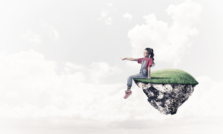 become: Cute smiling girl sitting on floating island high in sky