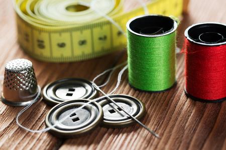 coil: imagen brillante de los accesorios del equipo de coser sobre la mesa de madera