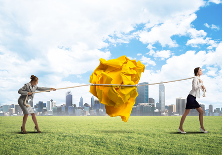 Two businesswomen outdoors playing tag of war game Stock Photo