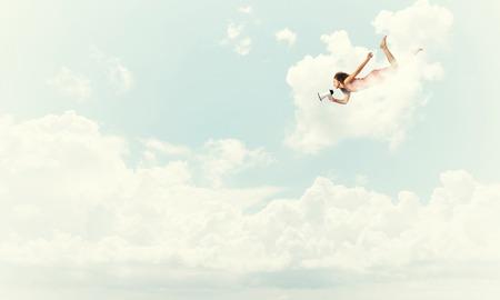 Jonge vrouw met megafoon vliegen hoog in de lucht Stockfoto