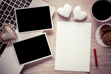 Laptop met koffie kop foto's en pen op houten tafel Stockfoto
