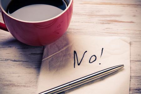 Kopje koffie en servet met bericht op houten tafel