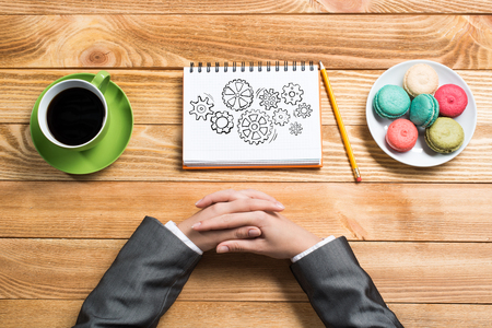 paper sheet: Top view of businesswoman hands and her sketch book on table