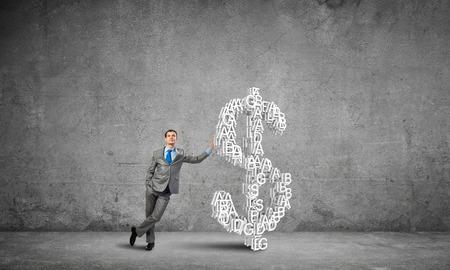 Young confident businessman leaning on big dollar sign Reklamní fotografie