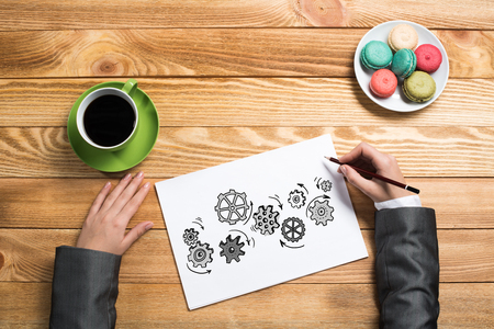 paper sheet: To view of businesswoman hands drawing on paper sheet gears mechanism