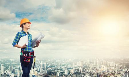 Ingenieursvrouw met blauwdruk op modern stadslandschap Stockfoto - 82402320