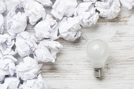 Many balls of crumpled paper and light bulb among them Stock fotó