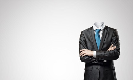 Headless businessman with arms crossed on chest in black suit Stok Fotoğraf - 82546445