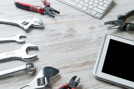 Set of industrial tools and tablet on wooden surface Stock Photo