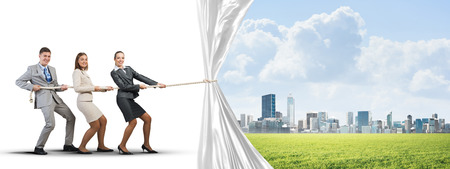 Three businesspeople pulling white blank fabric with rope Stock Photo