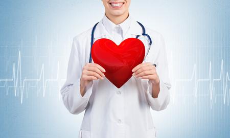 青い背景に赤い心を持って若い女性医師