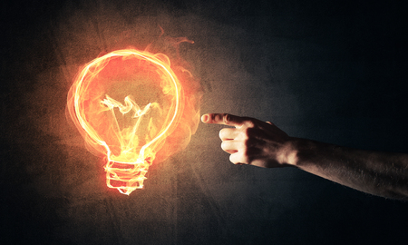 Close of man hand showing at glowing fire light bulb icon Stock Photo