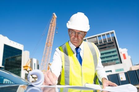Ingenieur man in de helm en jas beheersen van outdoor bouwplaats