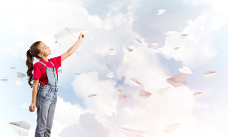 Little cute girl against sky background playing with paper airplane Stock Photo