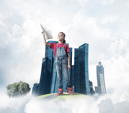 Cute kid girl on city floating island throwing paper plane Stock Photo