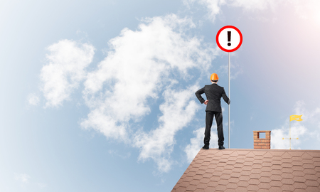 Young businessman with roadsign in hand standing on brick roof. Mixed media Stok Fotoğraf