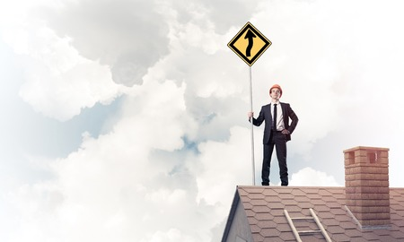 suburbian: Young determined businessman standing on house roof and showing yellow roadsign. Mixed media