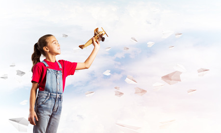 Little cute girl against sky background playing with retro airplane
