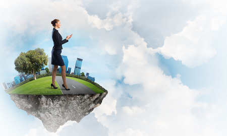 hands free phone: Elegant confident businesswoman standing on green floating island in blue sky