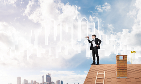 Young businessman in suit on roof edge. Mixed media Stock Photo