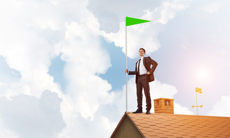 Businessman standing on house roof and holding green flag. Mixed media Stock fotó