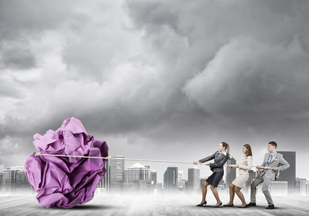 large group of business people: Office employees pulling together big crumpled paper ball Stock Photo