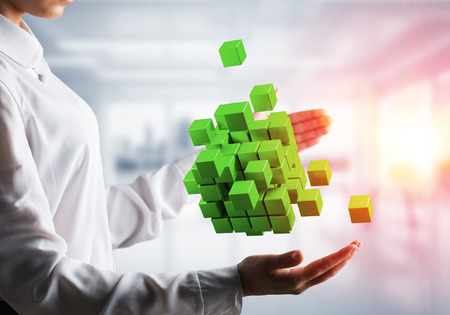 Cropped image of business woman hands holding multiple green cubes in hands with sunlight on office background. Stock Photo