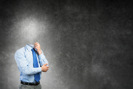 Empresario pensativo sin la cabeza en el fondo de hormigón Foto de archivo - 83463263