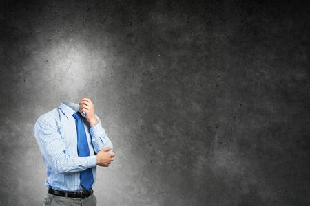 Peinzende zakenman zonder hoofd op concrete achtergrond Stockfoto