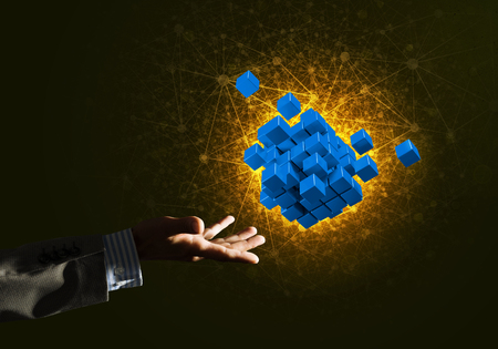 Close of businessman hand holding cube figure as symbol of innovation. 3D rendering Stock Photo