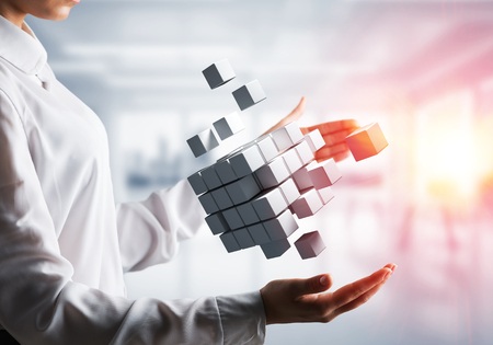 Cropped image of business woman hands holding multiple white cubes in hands with sunlight on office background. Mixed media. Stock Photo