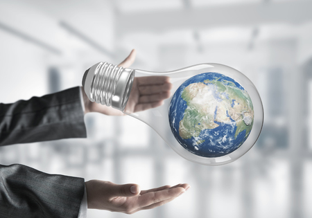 Cropped image of business woman hands holding lightbulb with Earth globe inside with office view on background. Elements of this image are furnished by NASA. Mixed media. Stock Photo