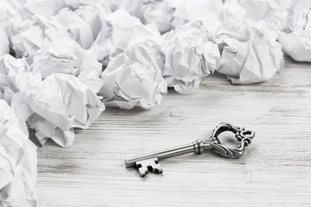Vintage key among many balls of crumpled paper Stock Photo