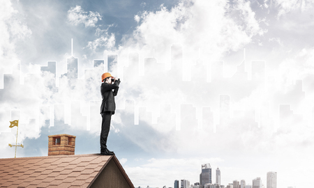 suburbian: Young businessman in suit and helmet on roof edge in search of something new. Mixed media