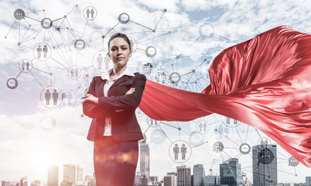 Young confident businesswoman wearing red cape against modern city Standard-Bild