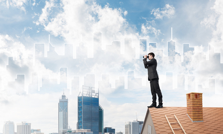 suburbian: Young businessman viewing cityscape in his binoculars Mixed media Stock Photo