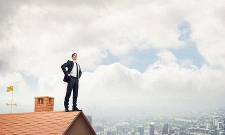 Jonge bepaald zakenman die op dak van het huis en kijkt weg. Gemengde media