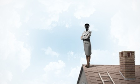 Faceless businesswoman with camera zoom instead of head standing on house roof Stock fotó