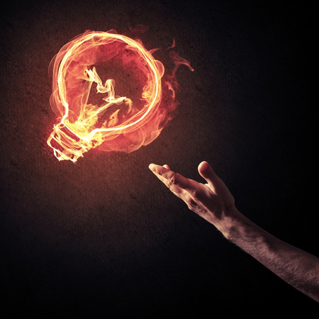 Close of man hand showing at glowing fire light bulb icon Stok Fotoğraf