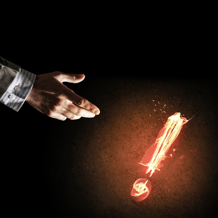 Businessman hand and fire glowing exclamation mark Stok Fotoğraf - 83950442